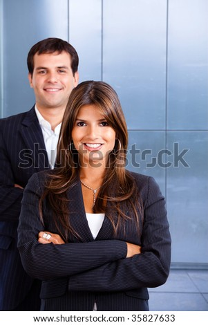 Business couple portrait smiling at an office