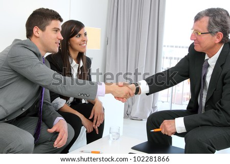 Business couple shaking hands with financial planner.