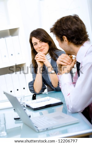 Business couple sitting at table, looking at each other and smiling.