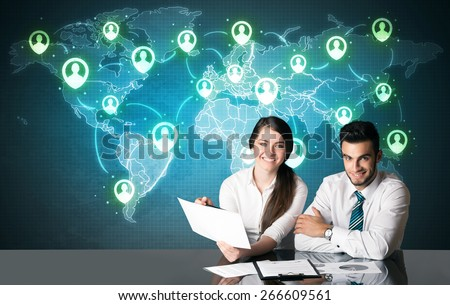 Business couple sitting at table with social media connection symbols on the world map
