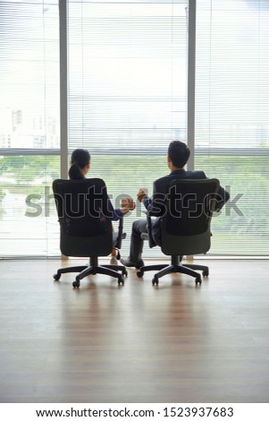 Business couple sitting in modern empty office, drinking coffee and enjoying cityscape, view from the back
