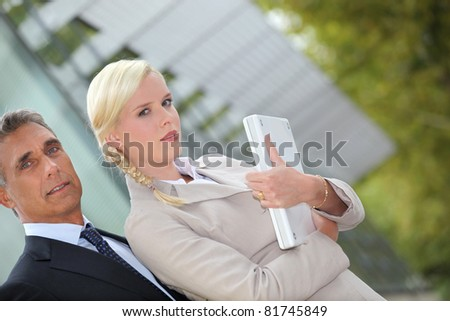 Business couple standing outside with a laptop