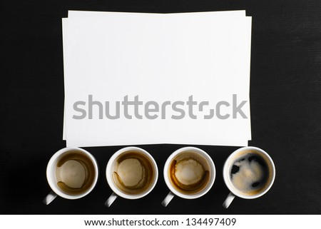 business creativity concept. empty and full cups of fresh espresso with blank paper on desk