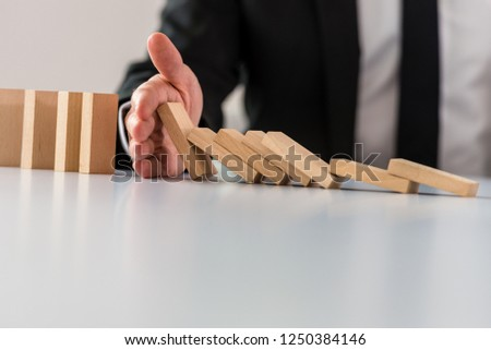 Business crisis solution concept with business manager intervening to stop collapsing dominos.