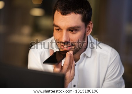 business, deadline and technology concept - happy businessman using voice command recorder on smartphone at night office