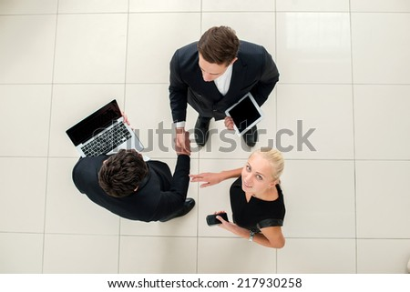 Business dealings. Top view of three business people in formal wear standing and discussing and shake hands