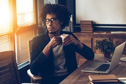 Business decision every day. Young handsome African man in glasses holding coffee cup and looking away while sitting at his working place
