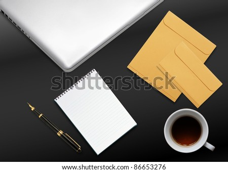 business desktop with laptop, notepad, envelops and mug of tea