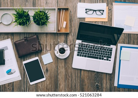 Business desktop workspace with laptop, digital tablet and paperwork, top view