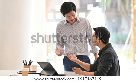 Business development manager discussing with his smart employee in black cotton shirt over the modern office background.