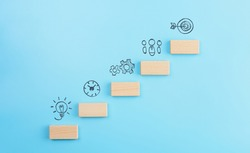 Business development strategy, Action plan and goal concepts, wooden cubes stacking as step stair with icons business strategy on blue background. copy space