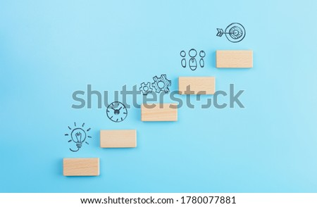 Business development strategy, Action plan and goal concepts, wooden cubes stacking as step stair with icons business strategy on blue background. copy space Сток-фото ©
