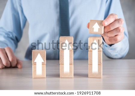 Business development to success and growing growth concept.businessman try to arrange wooden blocks into growing graphs