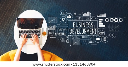 Business Development with person using a laptop on a white table #1131463904