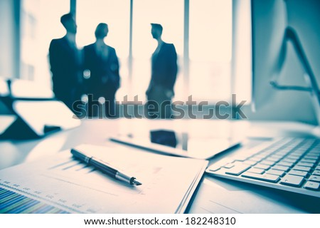 Business devices and documents at the workplace, unrecognized businesspeople sharing the ideas on the background  #182248310