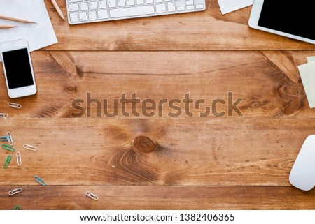 Photo of Business devices supplies on brown wooden desk, keyboard with phone, mouse and digital pc tablet modern gadgets stationery on office table workspace, workplace background, above top view copy space