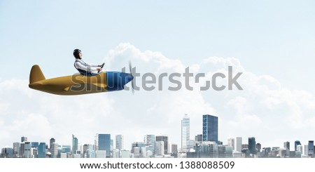 Business direction and motivation concept with pilot sitting in cabin of small airplane. Funny man in aviator hat and goggles driving propeller plane above city. Modern metropolis with high buildings #1388088509