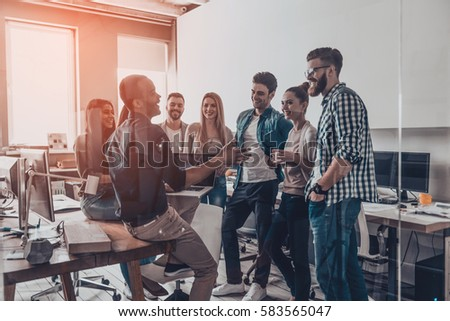 Business discussion.  Group of young modern people in smart casual wear having a brainstorm meeting while standing behind the glass wall in the creative office
