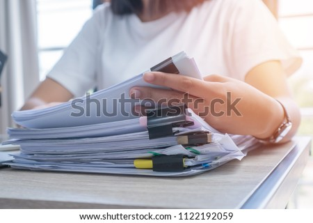 Business Documents concept : Employee woman hands working in Stacks paper files for searching and checking unfinished document achieves on folders papers at busy work desk office. Soft focus #1122192059