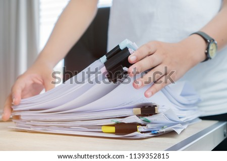 Business Documents concept : Employee woman hands working in Stacks paper files for searching and checking unfinished document achieves on folders papers at busy work desk office. Soft focus #1139352815
