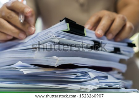Business Documents concept : Employee woman hands working in Stacks paper files for searching and checking unfinished document achieves on folders papers at busy work desk office. Soft focus #1523260907