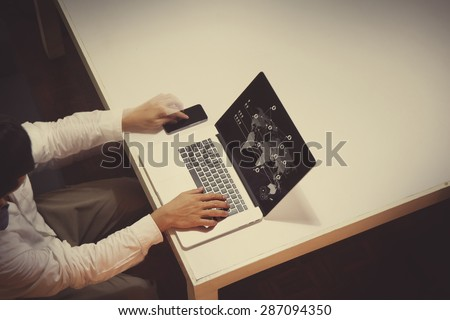 business documents on office table with digital tablet and man working with smart laptop computer background with overcast exposure effect with social media diagram
