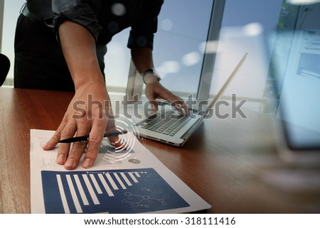 business documents on office table with smart phone and digital tablet and graph finance diagram and man working in the background - Shutterstock ID 318111416