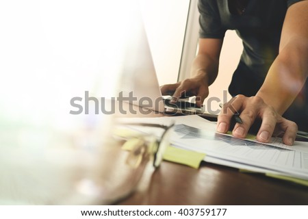 business documents on office table with smart phone and digital tablet and graph finance with social network diagram and man working in the background - Shutterstock ID 403759177