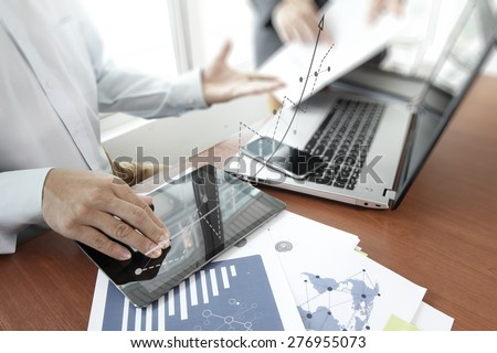 business documents on office table with smart phone and digital tablet and laptop computer and two colleagues discussing data  and graph business diagram  in the background