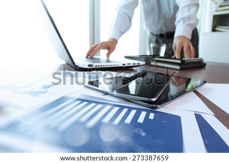 business documents on office table with smart phone and digital tablet and man working in the background - Shutterstock ID 273387659