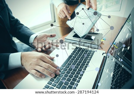 business documents on office table with smart phone and digital tablet and stylus and two colleagues discussing data in the background