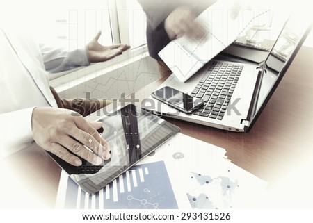 business documents on office table with smart phone and digital tablet and stylus and two colleagues discussing data in the background  with business graph diagram