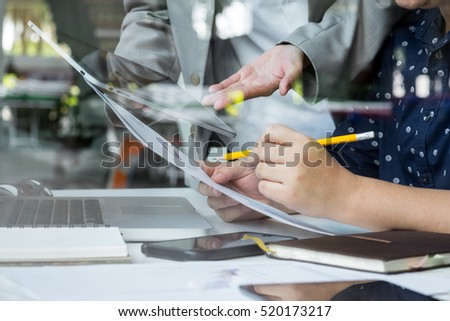 business documents on office table with smart phone and digital tablet and stylus and two colleagues discussing data in the background.