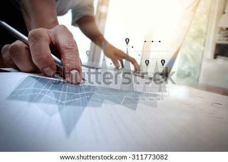 business documents on office table with smart phone and laptop computer and graph business with social network diagram and man working in the background
