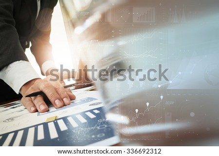 business documents on office table with smart phone and laptop computer and graph business with digital layer effect and man working in the background