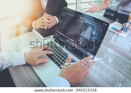 business documents on office table with smart phone and laptop computer and graph business with social network diagram and three colleagues discussing data in the background