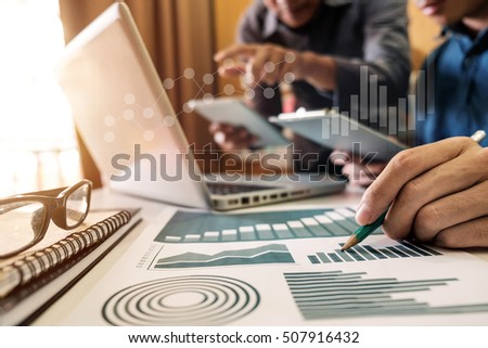 business documents on office table with smart phone and laptop computer and graph business with social network diagram and two colleagues discussing data in morning light