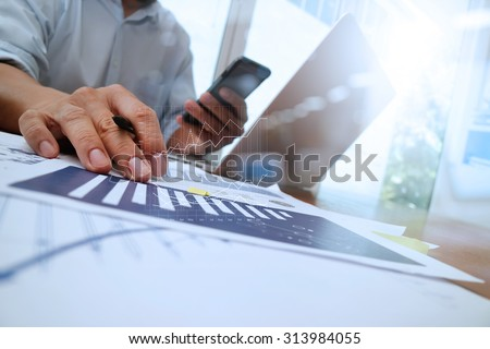 business documents on office table with smart phone and laptop computer and graph with social network diagram and man working in the background
