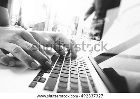 business documents on office table with smart phone and laptop computer and three colleagues discussing data in the background,black and white #492337327