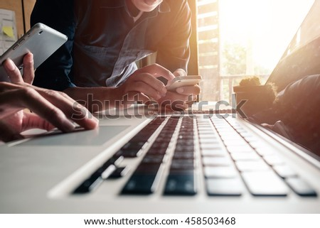 business documents on office table with tablet, smart phone and laptop and two colleagues discussing data in morning light - Shutterstock ID 458503468