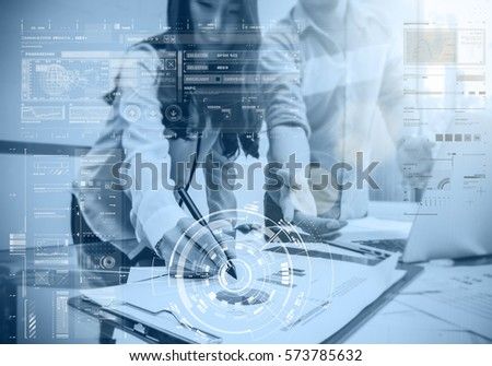 Business documents with laptop and technology digital virtual screen on the workplace with group of business teamwork working blurred background in the office meeting room