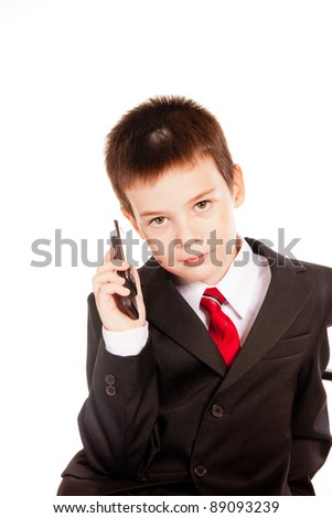 Business dress-code kid with a mobile phone posing in studio on white