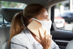 Business during coronavirus. Business woman wearing protective face mask talking by mobile phone while sitting on back seat in the car