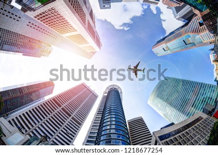 Business economy concept showing airplane flying over modern office skyscraper buildings in Singapore's business and financial district. #1218677254
