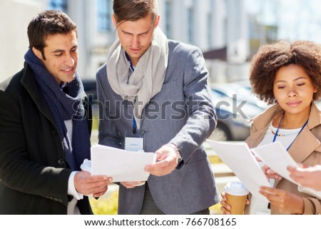 business, education and corporate concept - international group of people with papers and conference badges meeting outdoors #766708165