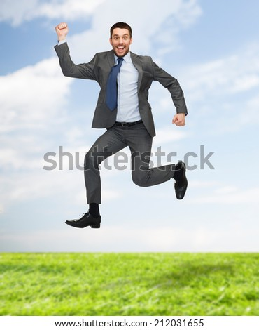 business, education and people concept - smiling happy businessman jumping