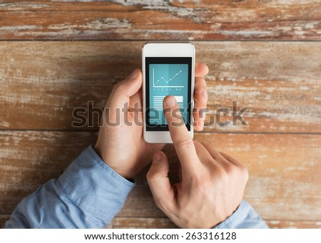 business, education, statistics, people and technology concept - close up of male hands holding smartphone and pointing finger to graph and text on screen at table
