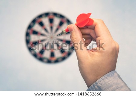 Business education success and target concept. Close up a hand is targeting the green dart arrow towards the center of dartboard. hit the target. Success in business. #1418652668