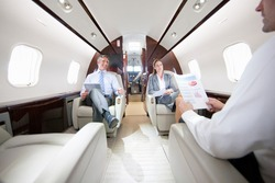 Business employees having a meeting while sitting in a private jet