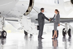 Business employees shaking hands beside a plane